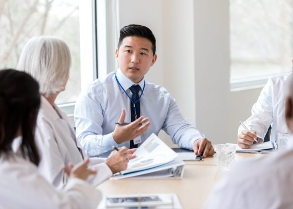 Male hospital administrator gestures while discussing a serious topic during a staff meeting.